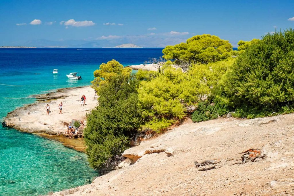 Greek island with pine trees and boats
