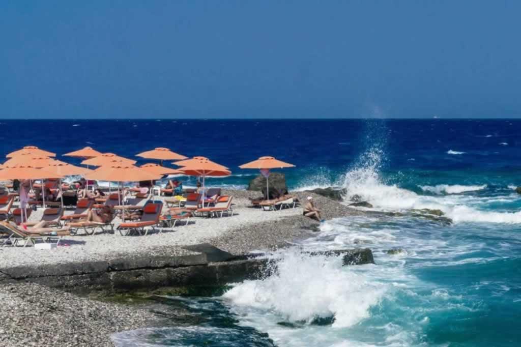 rhodes town beach orange umbrellas